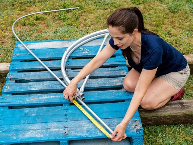 Niki inserts EMT conduit into a metal hoop bender