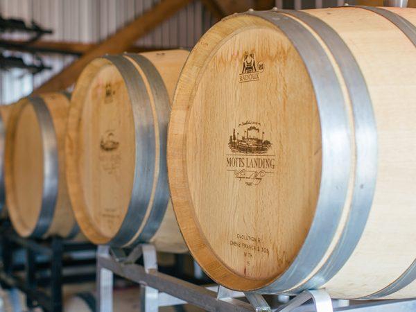 "Wooden barrels stamped ""Mott's Landing"" sit on their sides in a metal rack."